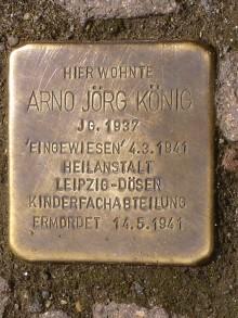 Bildinhalt: Ein sogenannter Stolperstein im Fußweg vor der heutigen Erich-Köhn-Straße 76 erinnert an Arno Jörg König. Er wurde nur 4 Jahre und 2 Tage alt.