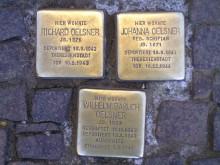 Bildinhalt: Drei sogenannte Stolpersteine vorm Haus im Fußweg an der Ecke zur Demmeringstraße erinnern an Johanna & Richard Oelsner und ihren Sohn Wilhelm Oelsner.