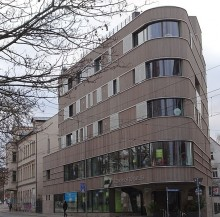 Bildinhalt: JANIK Ergonomische Bürowelten an der Zschocherschen Straße, unterhalb vom Felsenkeller. Holzhaus in Leipzig-Lindenau: Foto: wikipedia, Tnemtsoni (CC BY-SA 3.0)