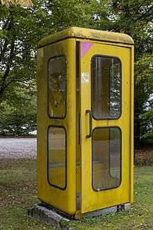 Bildinhalt: Auf dem Fußweg der Spittastraße neben der Backwaren-Verkaufsstelle stand in den 1990er Jahren eine solche öffentliche Telefonzelle. Bild: Olaf Kosinsky, Lizenz: CC BY-SA 3.0-de, Wikimedia Commons